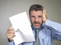 Stressed and overwhelmed 30s to 40s businessman in shirt and necktie stressed and overwhelmed with paper in his hand feeling upset stock image
