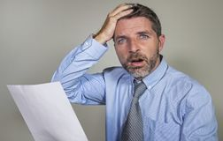 Stressed and overwhelmed 30s to 40s businessman in shirt and necktie stressed and overwhelmed with paper in his hand feeling upset stock photography