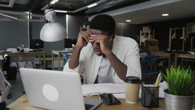 Stressed overworked black African business man working in his office at night