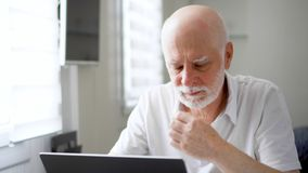 Stressed overworked tired senior man in white working on laptop at home. Rubbing his aching eyes. Stressed overworked tired senior man in white working on laptop stock footage