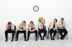 Stressed people waiting for a job interview. With a clown keeping up the good spirit Stock Photos
