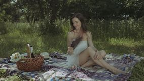 Pretty woman fighting heat waves with hand fan. Stressed pretty woman suffering a heatstroke refreshing with hand fan while sitting on the blanket in park on hot stock footage