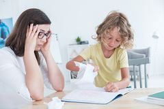 Stressed psychotherapist having a headache during a meeting with a rebellious child with behavioral disorders. The kid is tearing. Sheets of paper from the royalty free stock photography