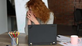 Stressed red haired woman working in the office. stock video
