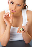 Stressed and sad brunette holds some pills. Stressed attractive young brunette holds some pills in her hand, isolated on white royalty free stock images