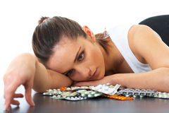 Stressed and sad brunette with some pills. Stressed attractive young brunette holds some pills, isolated stock image