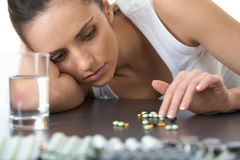 Stressed and sad brunette with some pills,isolated. Stressed attractive young brunette with some pills and glass of water stock images