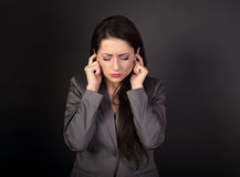Stressed sad business woman in grey suit closed her ears the fin. Gers because not want the hear any sounds and noise on dark grey background Stock Photos