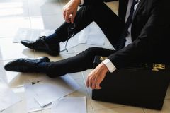Sad businessman sit on the floor. Stressed and sad businessman sitting on floor by scattered working paper files in empty office. Closeup suffer man lay on the Royalty Free Stock Photo
