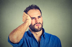 Stressed sad handsome young man looking up thinking. Portrait stressed sad handsome young man looking up thinking  on gray wall background. Human face Stock Image