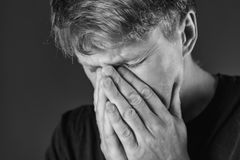 Stressed and sad man covering his face with hands. Sadness, despair, tragedy concept. Monochrome royalty free stock image