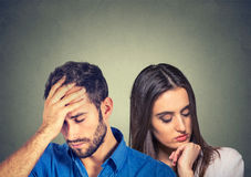 Stressed sad young couple man and woman looking down stock photos
