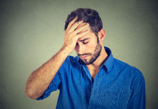 Stressed sad young man looking down  on gray wall background Royalty Free Stock Photo