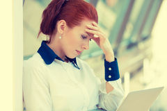 Stressed sad young woman with laptop standing in corporate office Royalty Free Stock Images