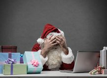 Stressed Santa connecting with his laptop. Stressed frustrated Santa Claus with head in hands connecting with his laptop, he is having computer problems on royalty free stock photo