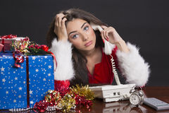 Stressed Santa girl at work. Stressed beautiful Santa girl sitting at desk and speaking on phone surrounded by Christmas presents, decorations, alarm clock and Royalty Free Stock Photos