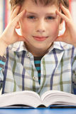 Stressed Schoolboy Studying In Classroom Royalty Free Stock Photos