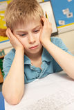 Stressed Schoolboy Studying In Classroom royalty free stock images