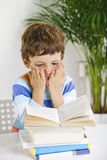Stressed schoolboy studying in home. Stock Photography