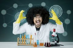 Stressed scientist doing chemical research. Image of Afro male scientist looks stressed while doing chemical research. Shot with virtual screen background Stock Photography