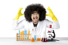 Stressed scientist doing chemical research on studio. Picture of Afro male scientist looks stressed while doing chemical research, isolated on white background Stock Photos