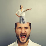 Stressed screaming man and smiley woman. Stressed screaming businessman with open head. young smiley businesswoman standing into the head and showing the Stock Photos