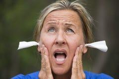 Stressed se preocupó a la mujer con los tejidos en oídos fotografía de archivo