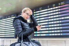 Stressed se preocupó a la mujer en la información del vuelo de comprobación del aeropuerto internacional sobre el teléfono elegan fotografía de archivo