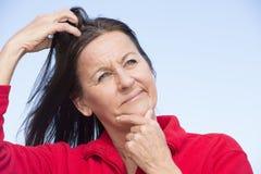 Stressed se preocupó a la mujer que rasguñaba la cabeza fotografía de archivo