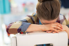 Stressed seamstress near sewing machine Stock Photo