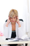 Stressed senior business woman sitting at table royalty free stock photography
