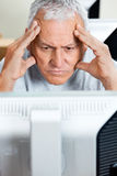 Stressed Senior Man Looking At Computer In Class Royalty Free Stock Image