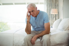 Stressed senior man sitting on bed Royalty Free Stock Photography