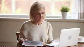 Stressed senior woman holding papers troubled with domestic bills stock video footage