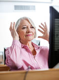 Stressed Senior Woman Looking At Computer In Classroom Royalty Free Stock Image
