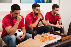 Stressed soccer fans watching a game. Portrait of a group of three friends and soccer fans feeling worried while watching a game on TV Stock Photo