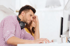 Stressed software developer at office. Deadline, startup, education, technology and people concept - sad stressed software developer or student with headphones Royalty Free Stock Photography