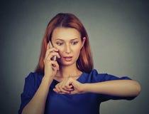 Stressed sorprendió a la mujer de negocios que miraba el reloj, corriendo tarde fotografía de archivo