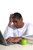 Stressed student. An attractive dark-skinned student in bad mood sitting in front of his notebook computer. All on white background Royalty Free Stock Photos