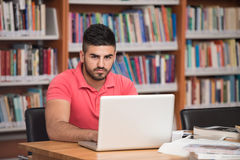 Stressed Student Doing His Homework At The Desk. Arabic Male College Student Stressed About His Homework Stock Photo