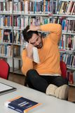 Bored Student With Books in Library. Stressed Student in High School Sitting at the Library Desk Stock Photography