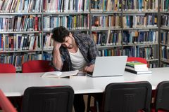 Confused Male Student Reading Many Books for Exam. Stressed Student in High School Sitting at the Library Desk Stock Image