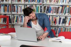Male College Student Stressed About His Homework. Stressed Student in High School Sitting at the Library Desk Stock Photography