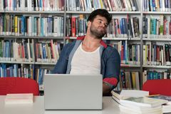 Unhappy Student With Too Much to Study. Stressed Student in High School Sitting at the Library Desk Royalty Free Stock Image