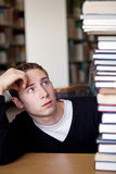 Stressed Student Looks At Book Pile. A frustrated and stressed out student looks up at the high pile of textbooks he has to go through to do his homework Stock Photography