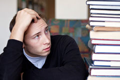Stressed Student Looks At Books. A frustrated and stressed out student looks up at the high pile of textbooks he has to go through to do his homework Royalty Free Stock Image