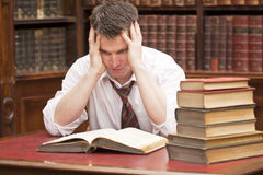 Stressed student with a pile of books to read Stock Images