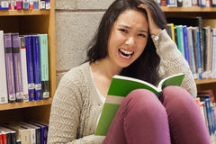 Stressed student reading in a library Stock Photos