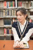 Stressed student sitting at a desk in library Stock Photos