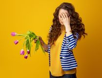 Stressed woman against yellow background with wilted flowers. Stressed stylish woman in striped jacket against yellow background with wilted flowers Stock Photography
